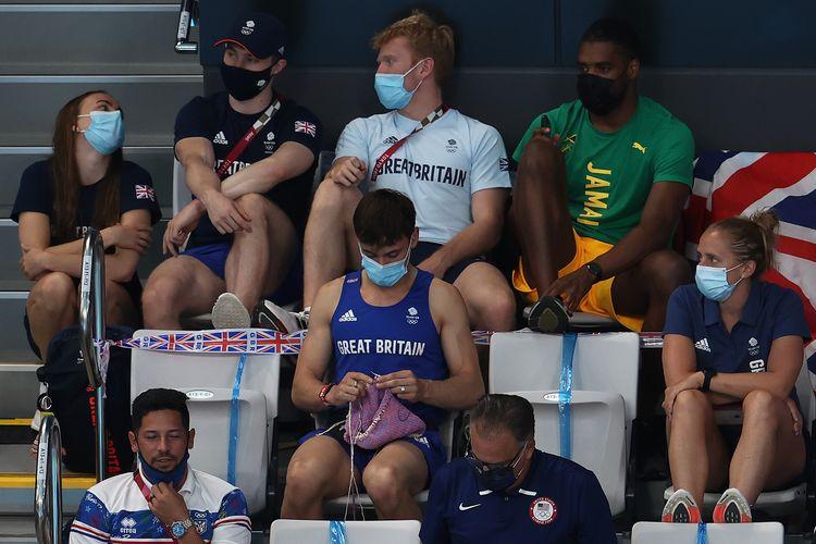 Atlet loncat indah asal Inggris, Tom Daley, terlihat menonton loncat indah kategori papan 3 meter putri dalam Olimpiade Tokyo sambil merajut pada Minggu (1/8/2021).