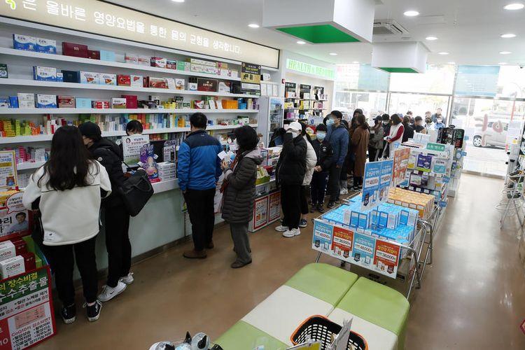 Antrean di sebuah apotek di Korea Selatan, saat virus corona mewabah dan ditetapkan WHO sebagai pandemi. Gambar diambil pada Minggu (15/3/2020).