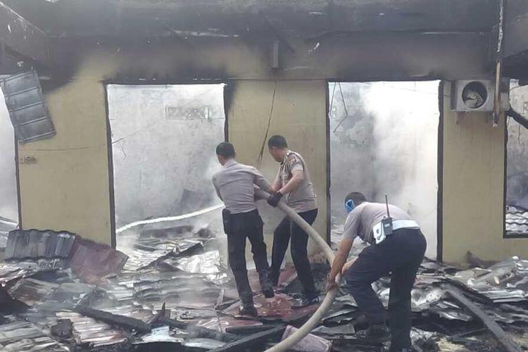 Petugas polisi melakukam pemadaman di salah satu ruang yang terbakar di Mapolres Ogan Ilir, Senin (17/1/2020)