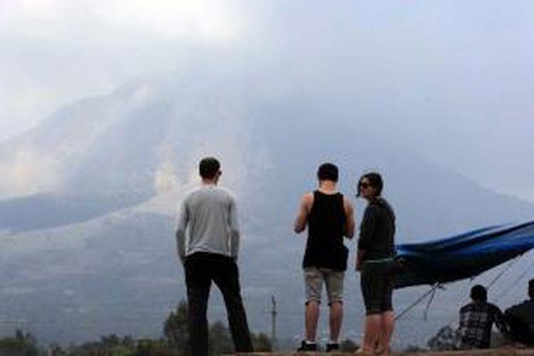 Sejumlah turis mancanegara mengamati Gunung Sinabung dari Desa Tiga Kicat, Karo, Sumut, Jumat (7/2/2014).