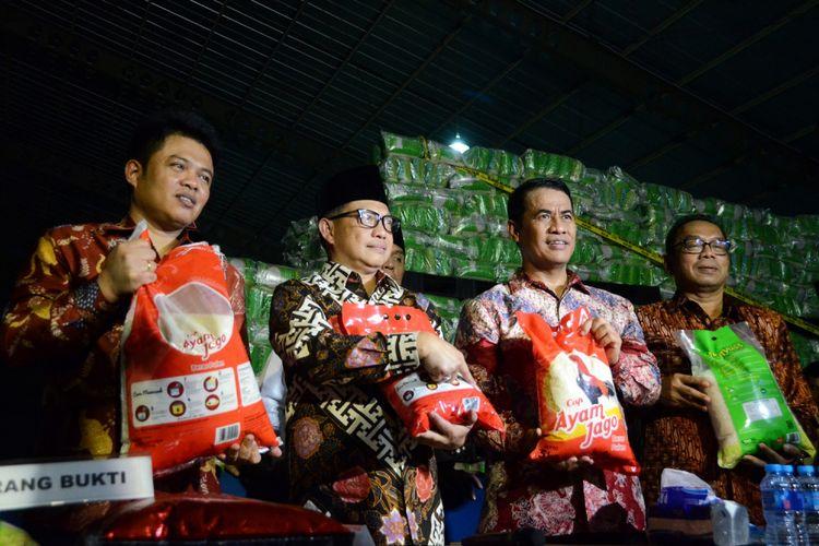 Kapolri Jenderal Tito Karnavian (kedua kiri) bersama Menteri Pertanian Amran Sulaiman (kedua kanan), Ketua Komisi Pengawas Persaiangan Usaha (KPPU) Syarkawi Rauf (kiri) dan Sekjen Kementerian Perdagangan Karyanto (kanan) menunjukkan karung berisi beras yang dipalsukan kandungan karbohidratnya dari berbagai merk saat penggerebekan gudang beras di PT Indo Beras Unggul, di kawasan Kedungwaringin, Kabupaten Bekasi, Jawa Barat, Kamis (20/7/2017) malam. Tim Satgas Pangan melakukan penggerebekan gudang dan ditemukan beras yang dipalsukan kandungan karbohidratnya sebanyak 1.162 ton dengan jenis beras IR 64 yang akan dijadikan beras premium yang nantinya akan dijual kembali dengan harga tiga kali lipat di pasaran, sehingga Pemerintah mengalami kerugian hingga Rp 15 triliun.