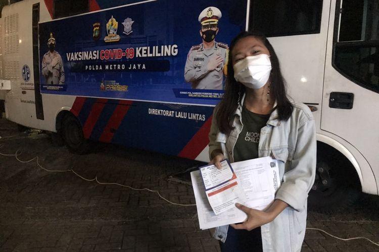 Salah satu warga di sekitar Kemang, Lia (23) mengantre untuk menjalani vaksinasi Covid-19 di dekat perempatan McDonalds Kemang, Bangka, Mampang Prapatan, Jakarta Selatan pada Selasa (29/6/2021) malam.