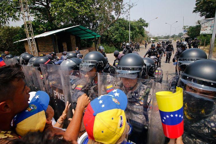 Pendukung oposisi Venezuela berhadap-hadapan dengan personil militer yang setiap pada Presiden Nicolas Maduro di perbatasan dengan Kolombia, Sabtu (23/2/2019).