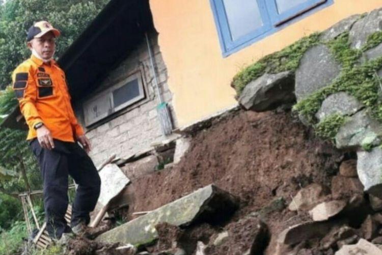 Seorang personel BPBD Cianjur meninjau salah satu rumah warga di Desa Rawabelut yang rusak akibat terdampak bencana pergerakan tanah.
