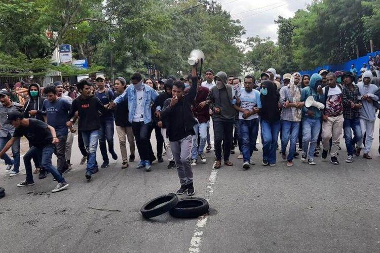 Ratusan mahasiswa Universitas Pattimura Ambon memblokade ruas jalan Ir M. Putuhena yang menghubungkan Kota Ambon dengan Bandara Internasional Pattimura saat menggelar aksi unjuk rasa di depan kampus mereka, Kamis (20/2/2020)