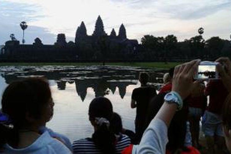 Sejumlah wisatawan mengabadikan panorama Candi Angkor Wat, Siem Reap, Kamboja, akhir Agustus 2013. Panorama candi ini tampak memukau pada pagi hari.