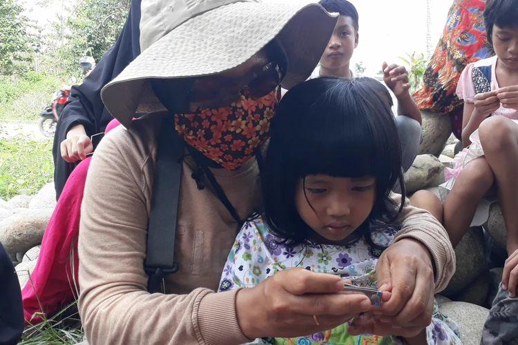 Seorang relawan melakukan potong kuku terhadap anak-anak pengungsi korban banjir Masamba, Luwu Utara, Sulawesi Selatan, kamis (23/07/2020).