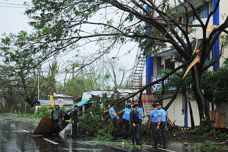 Polisi membersihkan pohon yang tumbang akibat Topan Kammuri di Legaspi City, Provinsi Albay, pada 3 Desember 2019. Dilaporkan dua orang tewas akibat terjangan topan, dan mengganggu agenda SEA Games sepanjang Selasa.