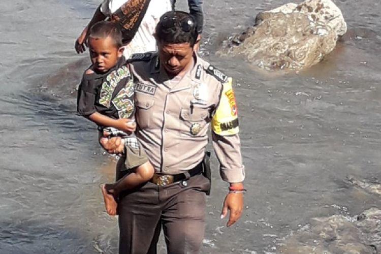 Bripka Safrul Senja Putra membantu warga menyeberangi di Kali Dagemage, Flores, NTT, Jumat (18/1/2019).