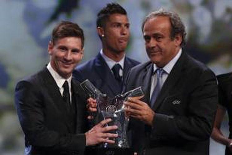 Bintang Barcelona, Lionel Messi (kiri), mengungguli bintang Real Madrid, Cristiano Ronaldo (belakang), dalam penghargaan Pemain Terbaik Eropa 2014-2015.