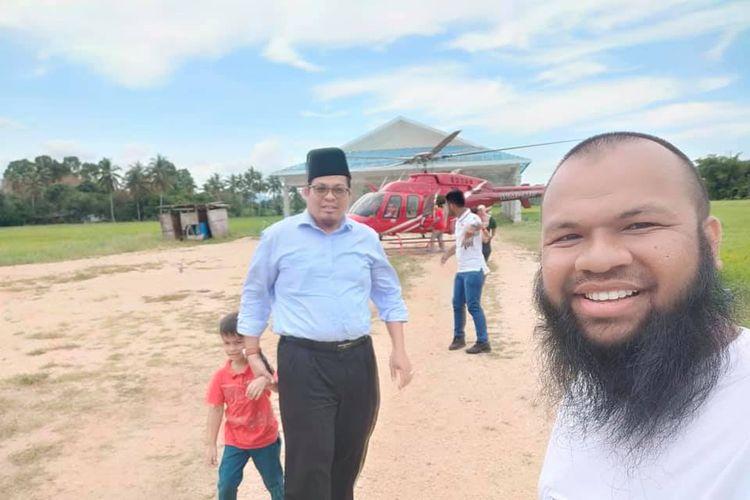 Muhammad Azlan Al-Amin (kanan) membawa helikopternya  ke kampung halamannya di sebuah desa di Besut, Terengganu, Malaysia. Dia di sana selama enam hari dan mengajak warga desa untuk naik helikopter secara gratis.