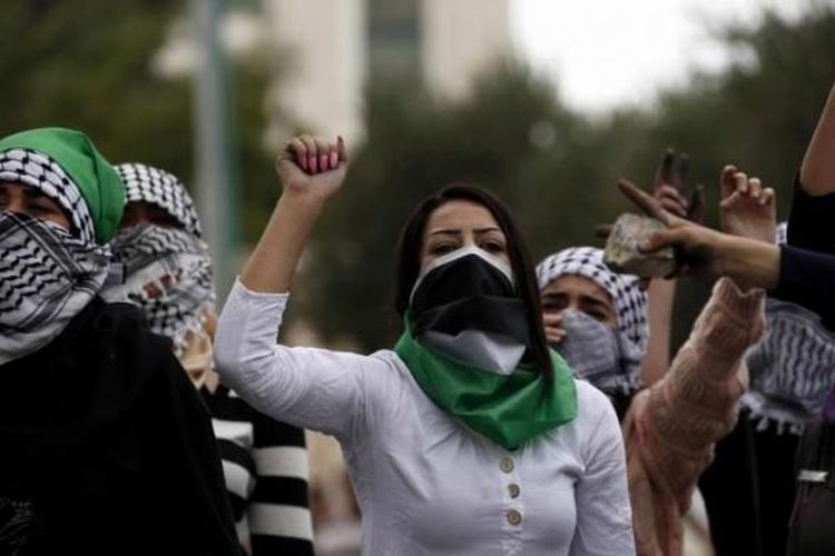 Perempuan Palestina memegang batu dan meneriakkan slogan saat bentrokan dengan tentara Israel di Beit El, Ramallah, Tepi Barat, 10 Oktober 2015.