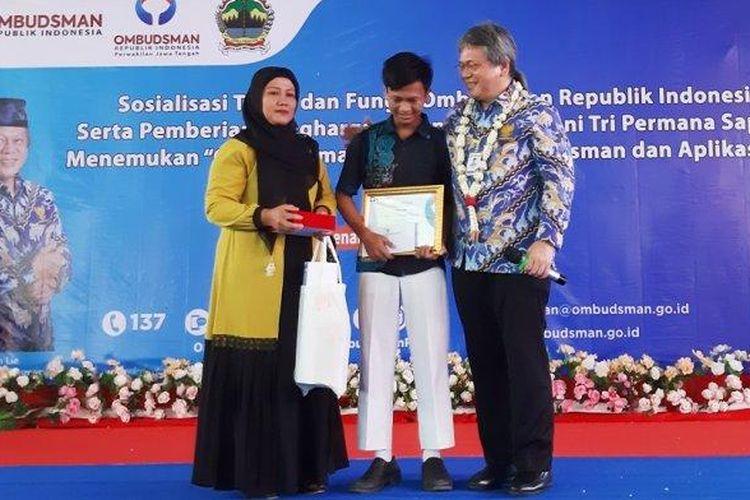 Suci Haryanti dampingi Deni Tri Permana Putra anak bungsunya terima penghargaan dari Ombudsman RI. Penghargaan diserahkan Anggota Ombudsman RI Alvin Lie, di Aula SMA N 1 Majenang, Rabu, (26/2/2020).