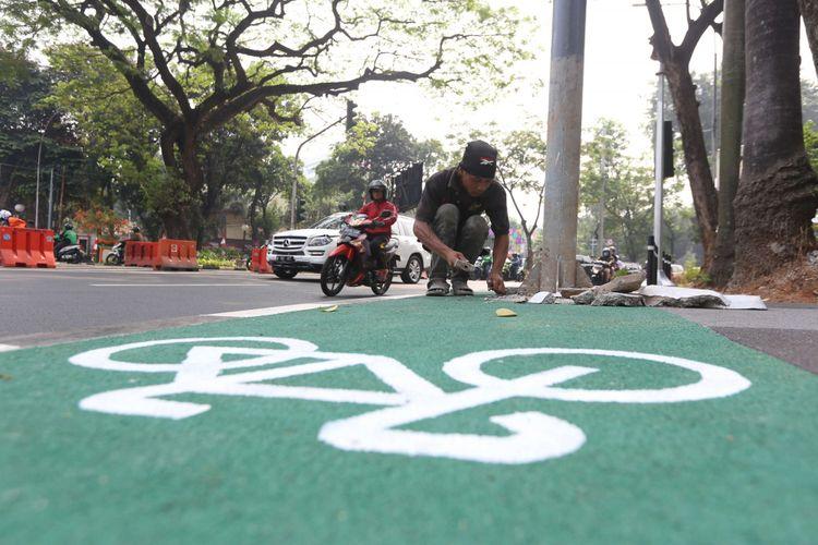 Pekerja akan memindahkan sejumlah tiang yang menghalangi jalur sepeda di Jalan Asia Afrika, Jakarta, Rabu (01/08/2018). Jalur sepeda di sepanjang jalan ini terhalang beberapa tiang lampu penerangan jalan umum (PJU), tiang lampu lalu lintas, hingga tiang rambu penunjuk jalan.