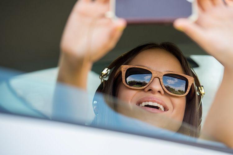 Ilustrasi seseorang sedang merekam gambar diri menggunakan kamera ponsel.