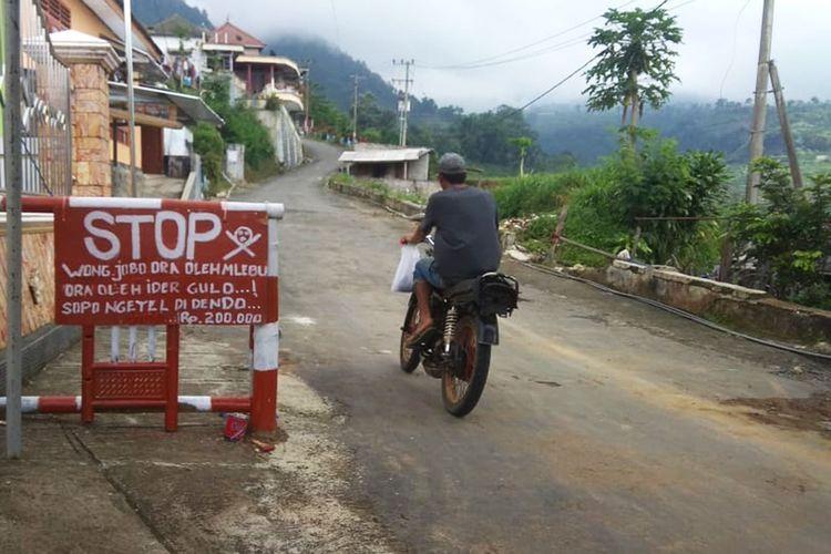 Papan pemberitahuan kepada warga terkait denda Rp 200.000 bagi warga Desa Gonggang yang nekat melakukan tradisi lebaran membagi gula kepada warga lainnya. Selain untuk mencegah penularan covid 19, larangan lebaran berbagi gula juga untuk meringankan perkonomian warga.