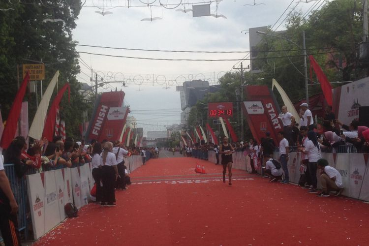 Seorang pelari mencapai garis finis Semarang 10K di Jalan Pemuda, Semarang, Minggu (16/12/2018).