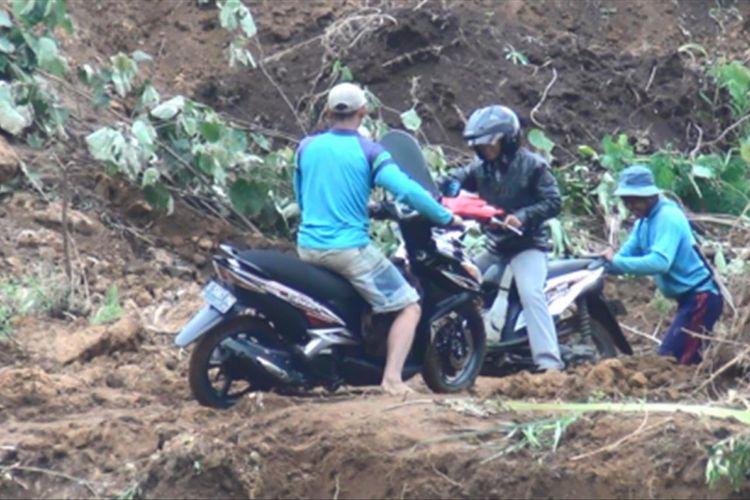 Sejumlah pengendara nekat melintas di atas material longsor meski kondisi tanah masih dalam status bahaya terjadi longsor susulan, Selasa (23/1/2018).