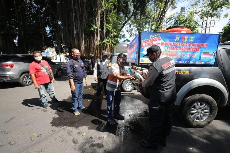 Pendekar Waras menyemprotkan handsanitizer warga sebelum masuk ke fasilitas pelayanan umum