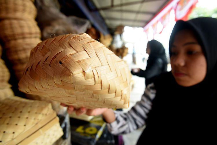 Seorang calon pembeli mencermati besek bambu yang dijual di sebuah kios di Jalan Jatinegara Barat, Jakarta Timur, Sabtu (10/9/2019). Sejumlah pedagang mulai  menjual besek yang terbuat dari bambu untuk membungkus daging kurban saat Idul Adha.