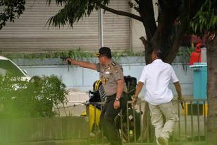 Polisi melepas tembakan ke arah terduga pelaku yang berada di luar sebuah kafe setelah ledakan menghantam kawasan Jalan MH Thamrin, Jakarta Pusat, 14 Januari 2016. Serangkaian ledakan menewaskan sejumlah orang, terjadi baku tembak antara polisi dan beberapa orang yang diduga pelaku.