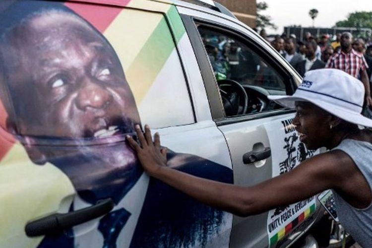 Warga Zimbabwe pendukung pemerintahan baru menyentuh gambar calon presiden baru Emmerson Dambudzo Mnangagwa.