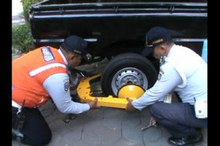 Petugas mengunci roda mobil yang parkir di area citywalk di Solo, Jumat (20/9/2013).