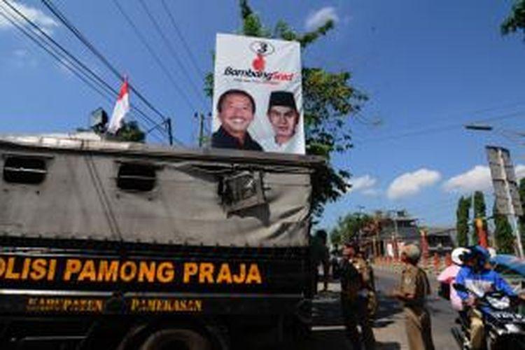 Anggota Pol PP Pamekasan menertibkan alat peraga di sejumlah jalan protokol di dalam kota Pamekasan saja. Sementara di pedalaman masih belum tersentuh.