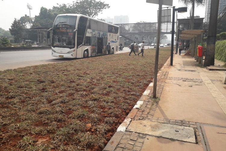 Dua orang penumpang bus nekat menyeberangu area rerumputan yang memisahkan halte bus di depan Gedung Graha CIMB Niaga, Senayan, dengan Jalan Jenderal Sudirman, Selasa (24/7/2018).