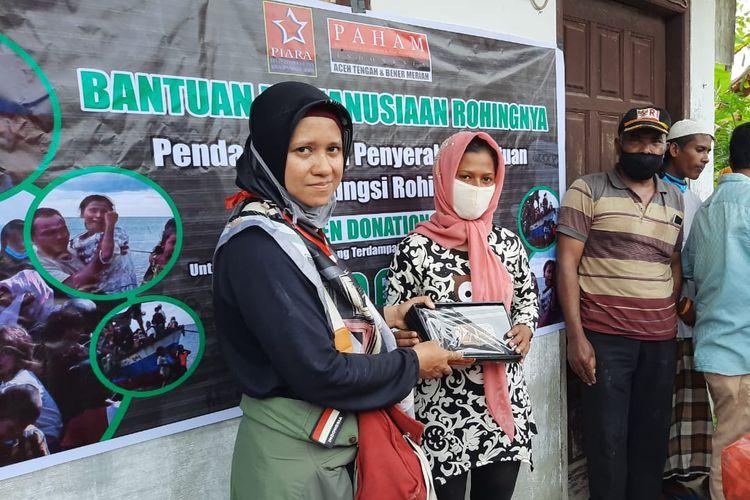 Relawan PIARA dan Direktur Pos PAHAM Aceh Tengah dan Bener Meriah, Nikmah Kurnia Sari, saat menyerahkan bantuan kepada pengungsi Rohingya di Aceh Utara, Munggu (28/6/2020).