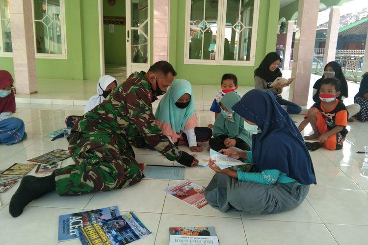 Sertu Tarmudji, Babinsa Desa Majalaya, Kecamatan Majalaya, Kabupaten Karawang di antara anak-anak yang tengah membaca, Selasa (30/6/2020).