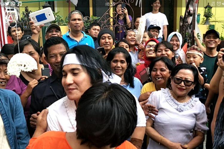 Vino G Bastian mencium pipi seorang ibu yang menjadi pemenang lomba makan kerupuk di kawasan Kampung Bali, Kebon Sirih, Jakarta Pusat, Jumat (17/8/2018).