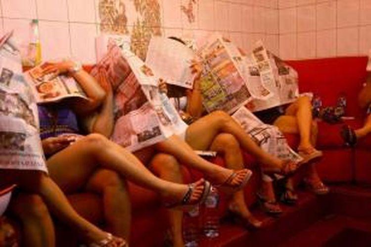 Pekerja seks menutup wajah mereka dengan koran saat polisi militer melakukan patroli di kawasan Dolly, Surabaya, 3 Mei 2014. Wali Kota Surabaya Tri Rismaharini telah menetapkan menutup kawasan bordil di Dolly pada 18 Juni 2014.
