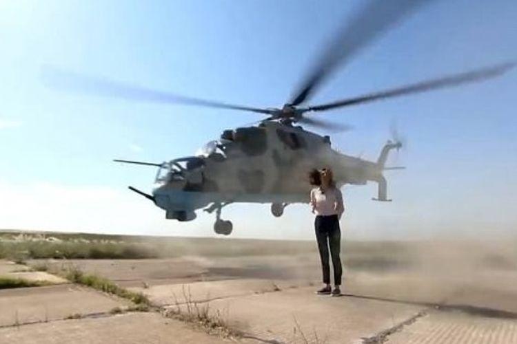 Tangkapan layar dari rekaman saat sebuah helikopter tempur dan nyaris menyambar tubuh reporter perempuan yang sedang menyampaikan laporan di tengah landasan terbang di markas militer Azerbaijan.