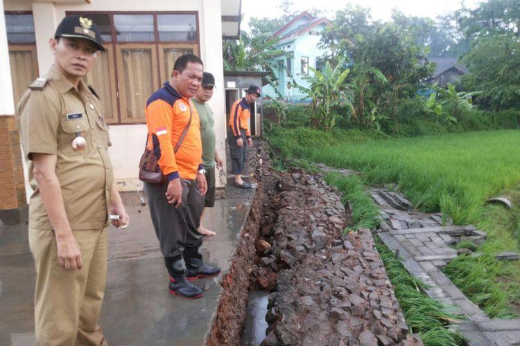 Ketua BPBD Heru Subroto (dua dari kiri) tengah meninjau lokasi banjir. Derasnya air membuat pagar SD Leyangan 1 ambruk.