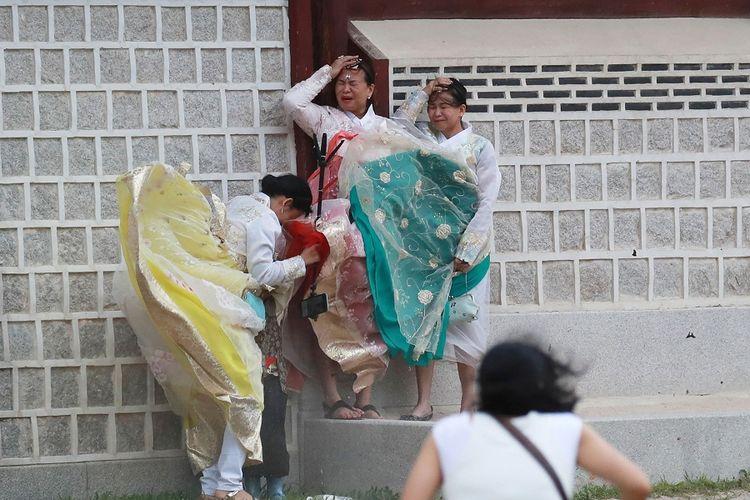 Pengunjung di Seoul berjuang menahan tiupan angin kencang saat Topan Lingling mendekati wilayah Korea Selatan, Sabtu (7/9/2019).