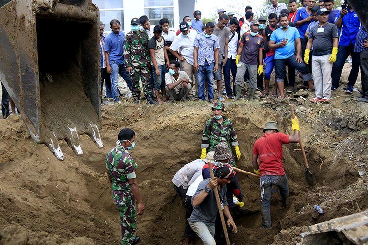 warga bersama sejumlah personil TNI sedang mengangkat jenazah korban tsunami yang berada di lahan pembangunan klinik, di Desa Kajhu, Kecamatan Baitussalan,  Kabupaten Aceh Besar. Rabu (19/02/2019).