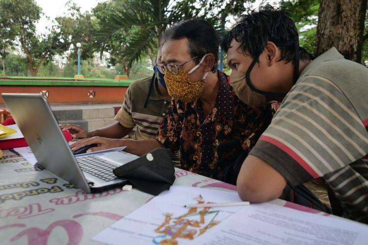 Guru SMPLB Dharma Wanita Kota Madiun, Purwanto Tri Wahono (58) memberikan pelajaran anak-anak berkebutuhan khusus di meja warung makan di masa pandemi covid-19