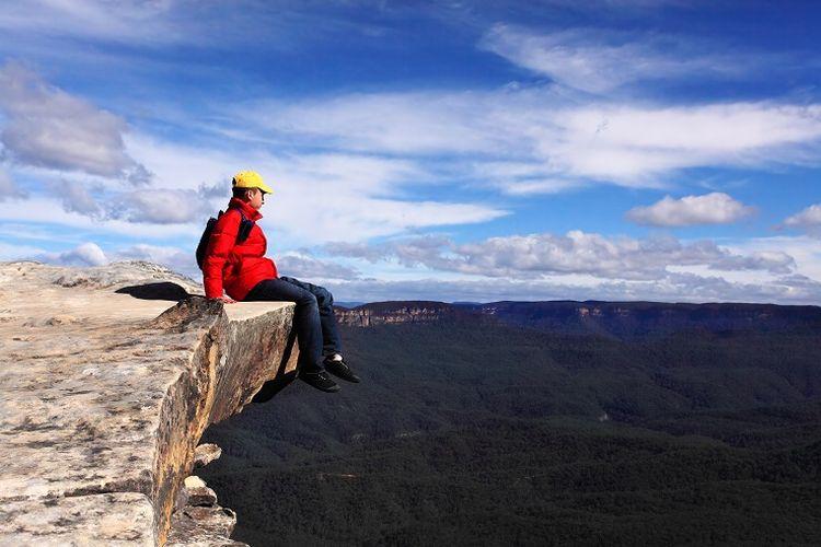 Ilustrasi Wisatawan - Seorang wisatawan sedang duduk di Lincolns Rock di Blue Mountains, Australia.