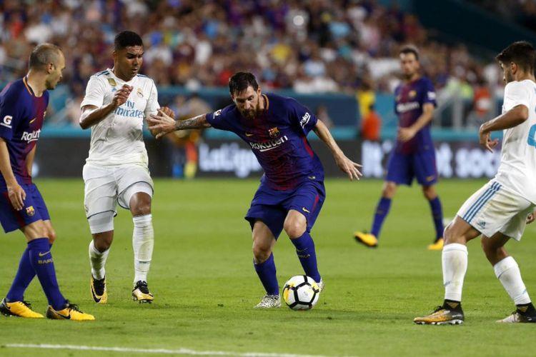 Lionel Messi mencoba lepas dari pengawalan pemain belakang lawan saat Barcelona berhadapan dengan Real Madrid dalam ICC 2017 di Stadion Hard Rock Miami, Sabtu (26/7/2017).