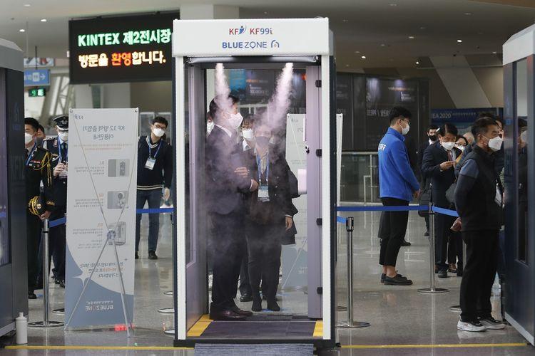 Seorang pengunjung menunggu giliran untuk masuk ke bilik disinfektan di DX Korea 2020, Goyang, Korea Selatan, pada Rabu (18/11/2020).
