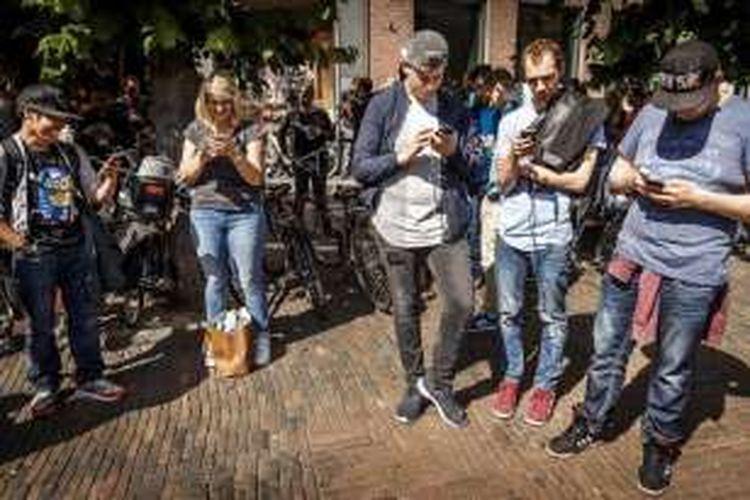 Gamer bermain dengan aplikasi Pokemon Go di ponsel mereka, di Grote Markt, Haarlem, Belanda, Rabu (13/7/2016).