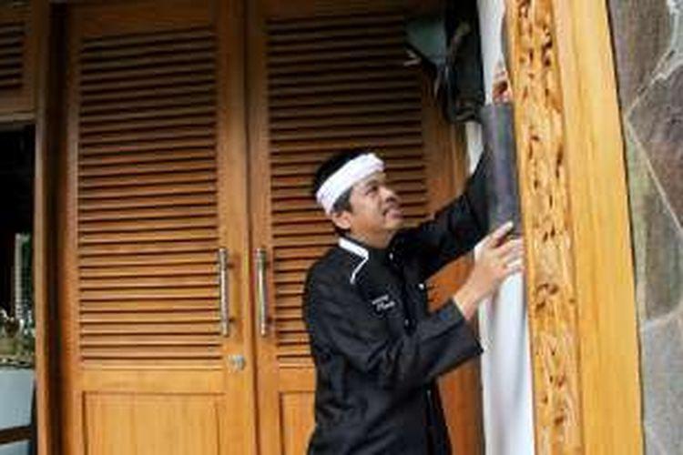 Bupati Purwakarta Dedi Mulyadi memasang bambu tempat penyimpanan beras perelek.