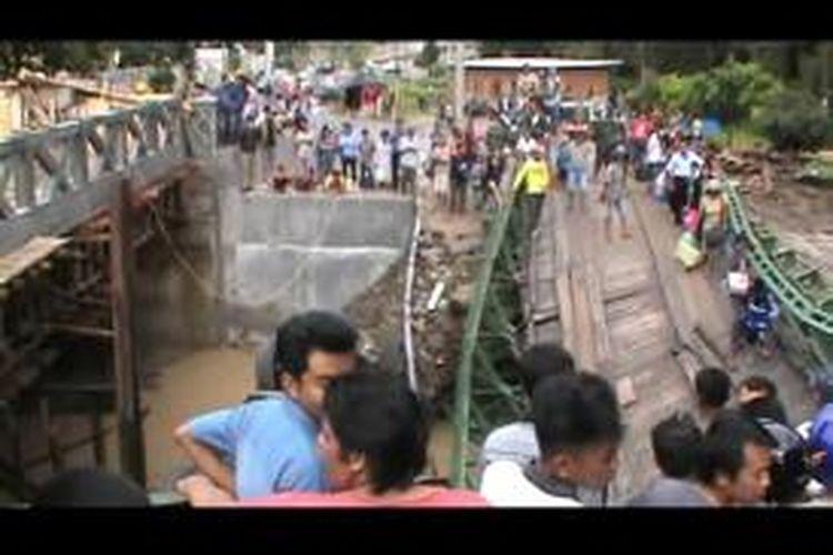 Warga terpaksa meniti jembatan di Nagori Marihat Baris, Kecamatan Siantar, Simalungun, yang ambles, Sabtu (22/11/2014) malam. Jembatan ambles setelah dilewati satu truk bermuatan aspal. Truk jatuh ke sungai.