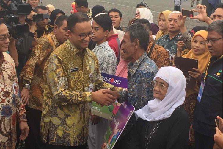 Gubernur DKi Jakarta Anies Baswedan membagikan secara simbolis Kartu Lansia Jakarta kepada sejumlah lansia di Halaman Monumen Nasional (Monas), Kamis (21/12/2017)