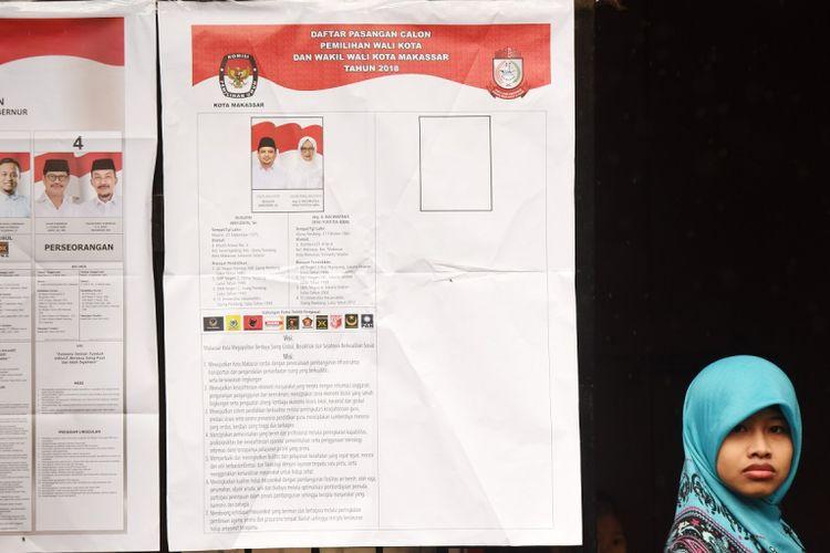 Warga melintas di dekat daftar pasangan Calon Gubernur-Wakil Gubernur Sulsel dan Calon Walikota-Wakil Walikota Makassar saat pemungutan suara pemilihan Gubernur-Wakil Gubernur Sulsel dan Walikota-Wakil Walikota Makassar di TPS 01 Keluarahan Tidung Mariolo Makassar, Sulawesi Selatan, Rabu (27/6).  Warga Makassar melakukan pemilihan Calon Gubernur dan Wakil Gubernur Sulsel 2018 yang diikuti empat pasang calon dan Calon Walikota-Wakil Walikota Makassar yang diikuti satu pasang calon.  ANTARA FOTO/Yusran Uccang/ama/18