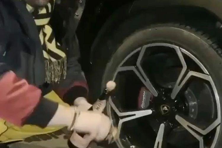Screengrab video TikTok yang menampilkan Victor Micula mencuci ban Lamborghini miliknya dengan dua botol sampanye.