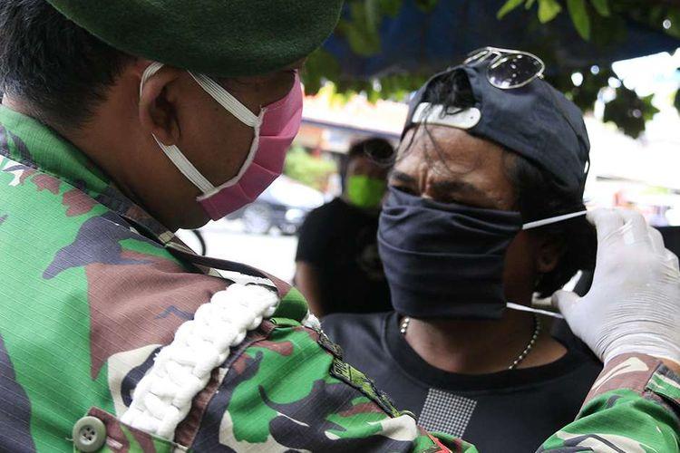 Personel TNI dari Kodim 0101 Aceh Besar membagi-bagikan masker dan nasi bungkus kepada warga di Kota Banda Aceh, di tengah pandemi virus corona (Covid-19), Sabtu (18/4/2020). Kegiatan bagi-bagi masker dan nasi bungkus itu menyasar kalangan masyarakat kurang mampu di antaranya pengemudi becak, tukang tambal ban, nelayan, dan pemulung.