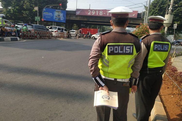Polisi berjaga di kawasan ganjil genap di Fatmawati, Jakarta Selatan