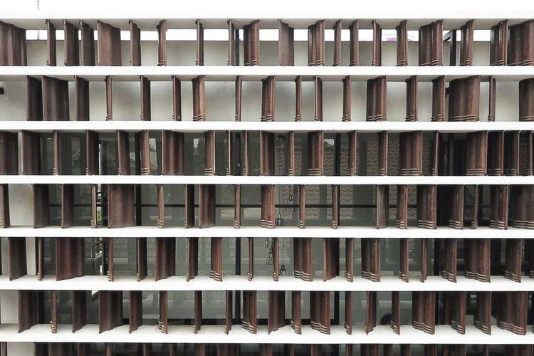 Deretan genteng yang ditata berdiri menciptakan efek fasad yang unik.
